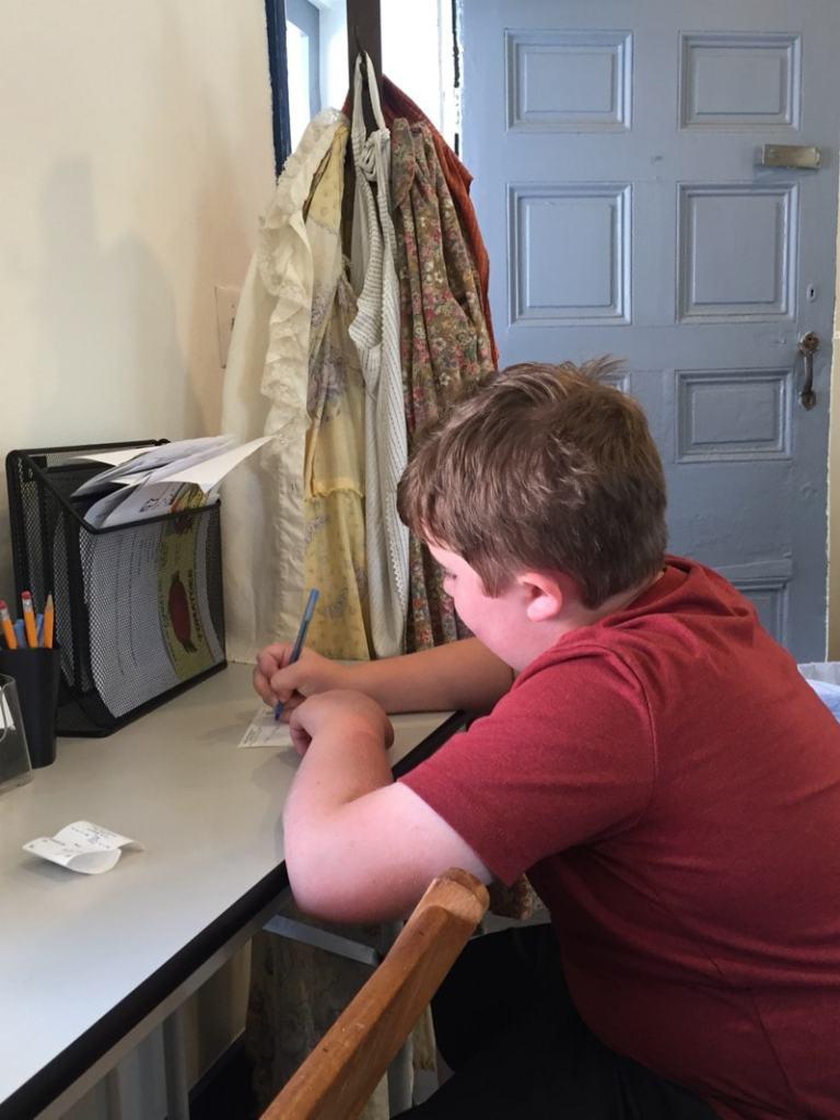 Evan writing a postcard