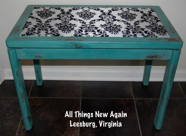 Table painted turquoise with black and white damask fabric on tabletop