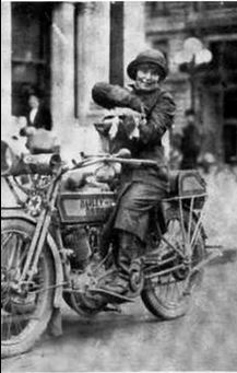 Della Crewe and her dog Trouble. There is a disk brake on the front wheel of her bike - it is actually a Corbin speedometer / odometer.