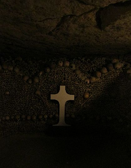 A cross and three mounds of bones in the Paris Catacombs.