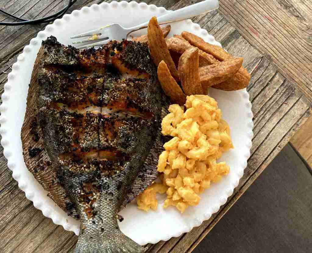 Flounder cooked up on a plate with sides.