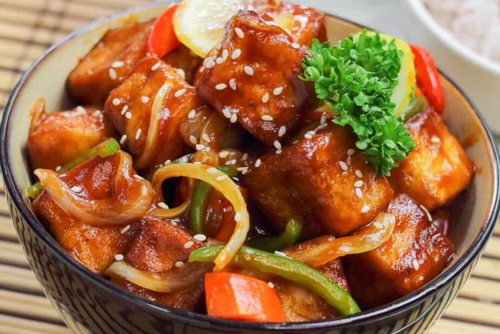 A low-angle shot of Sweet and Sour Tofu in a bowl.