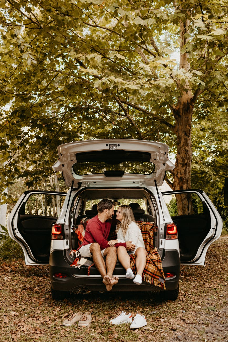 photo of couple sitting in the back of car