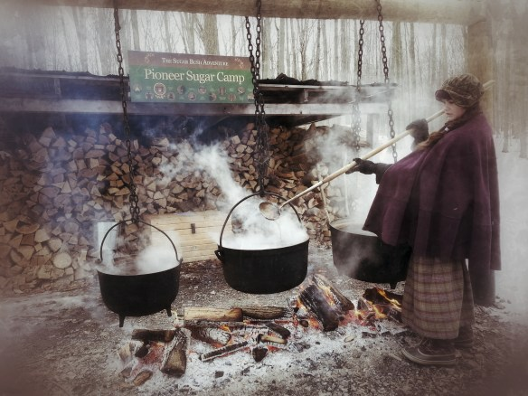 Woman stirring cauldrons of sap