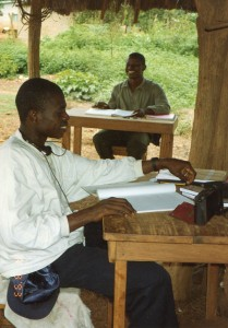 Augustin and Bertin Sit at Work Tables, Smiling, 8-9-93