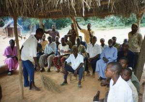 Kosangbe meeting under hangar - man sweeps ground - San Kofi and San Yao and male elders 1 - 8-14-93