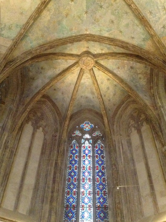 The now-faded ceiling and stained glass of Holy Cross
