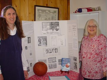 #9b Susan Steere and Mary Ellen Westlake by the John Family display – featuring the book written by Gene Johnson's son, Jim Johnson: A COACH AND A MIRACLE