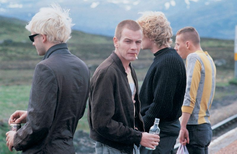 Four main characters on a train platform in the Scottish countryside in the film Trainspotting (1996)