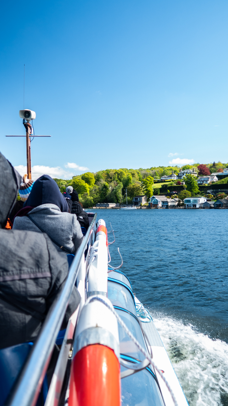 Side of a boat with islands in the background on Lake Windermere in Bowness-On-Windermere in the Lake District, UK