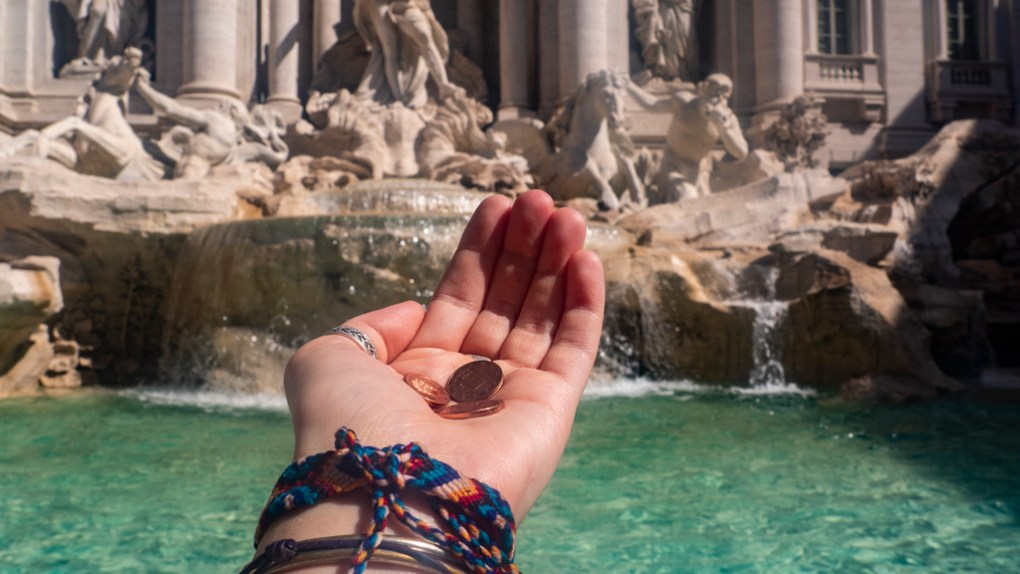 Throwing three coins in the Trevi Fountain in Rome, Italy