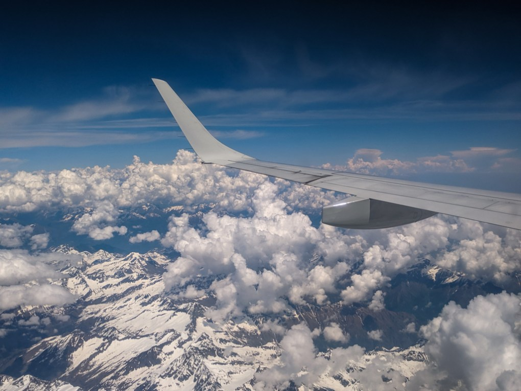 Plane wing of Ryanair plane over the Alps travelling to Milan