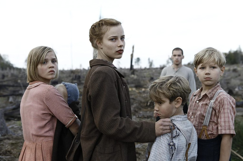 Film still from Lore (2012) of melancholic young adults and children in a barren land