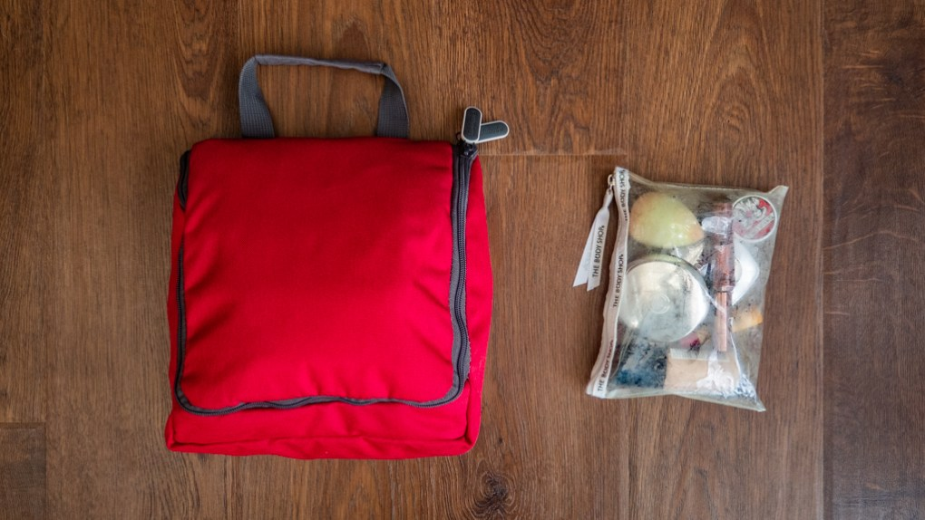 Flatlay of Noom toiletries bag and make-up in a clear pouch