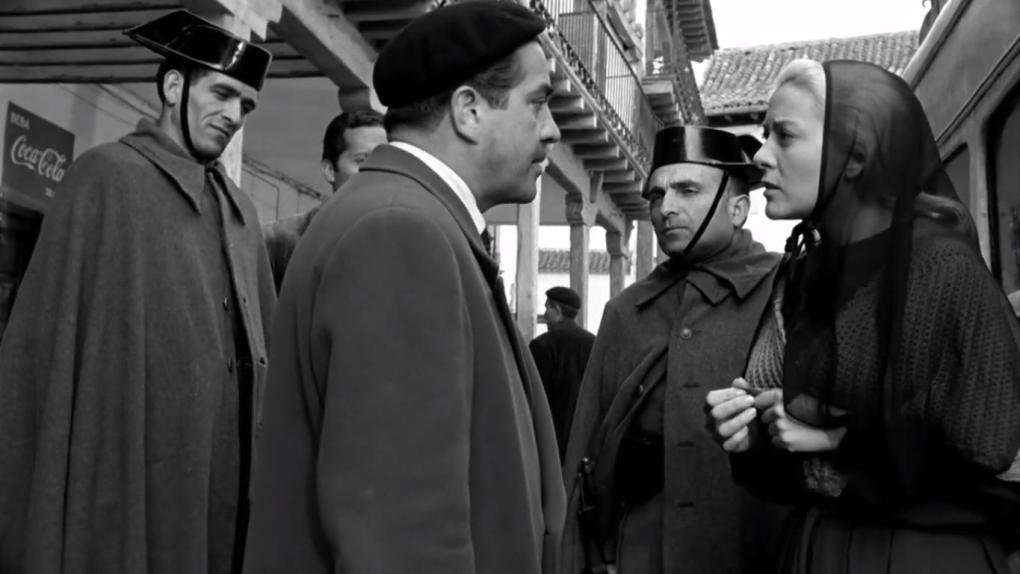 Viridiana (1961) black and white film still of a nun talking to a group of men in Madrid, Spain