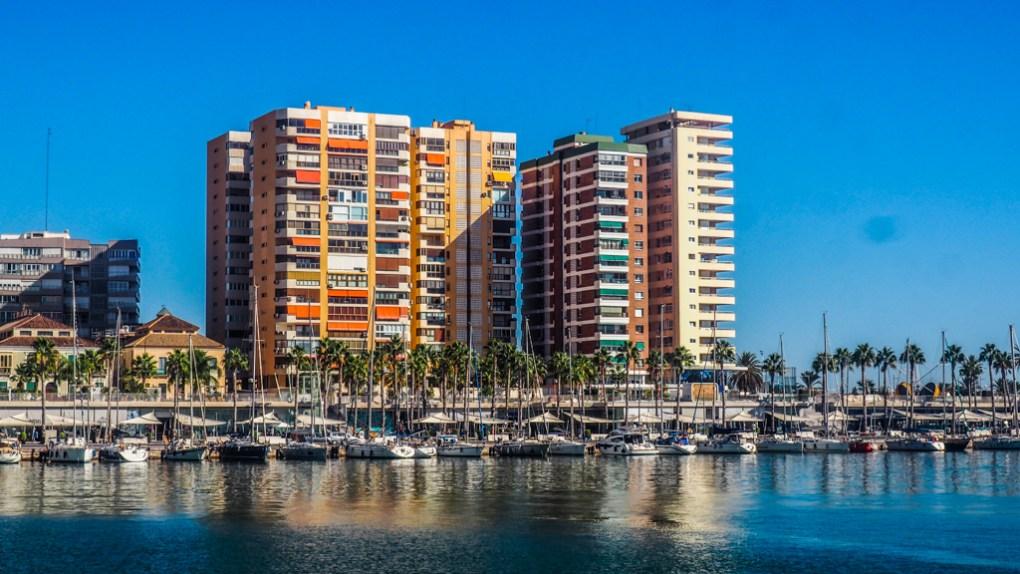 High Rise apartments, palm trees and boats lining Port de Málaga, Spain