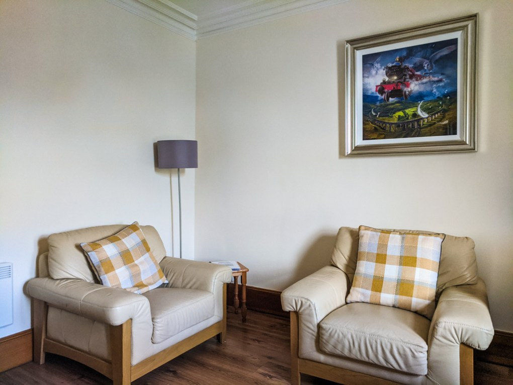 Fort William Apartment Interior with white lounge chairs and Hogwarts Express painting in Scotland