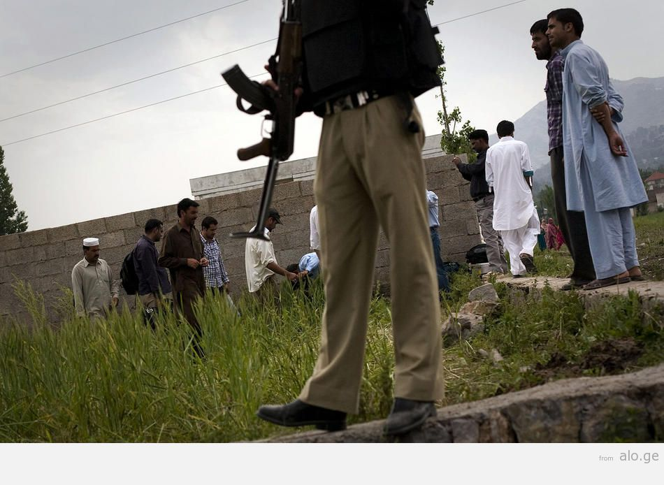 A Pakistani policeman watches over media and onlookers outside the compound where Osama bin Laden was killed.