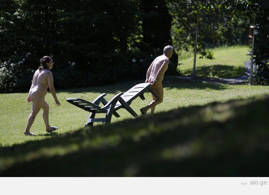 """A couple walks with a deckchair during the """"www.inudisti.it"""" web community's annual gathering on private property at Oasis of Zello naturist resort near Bologna"""