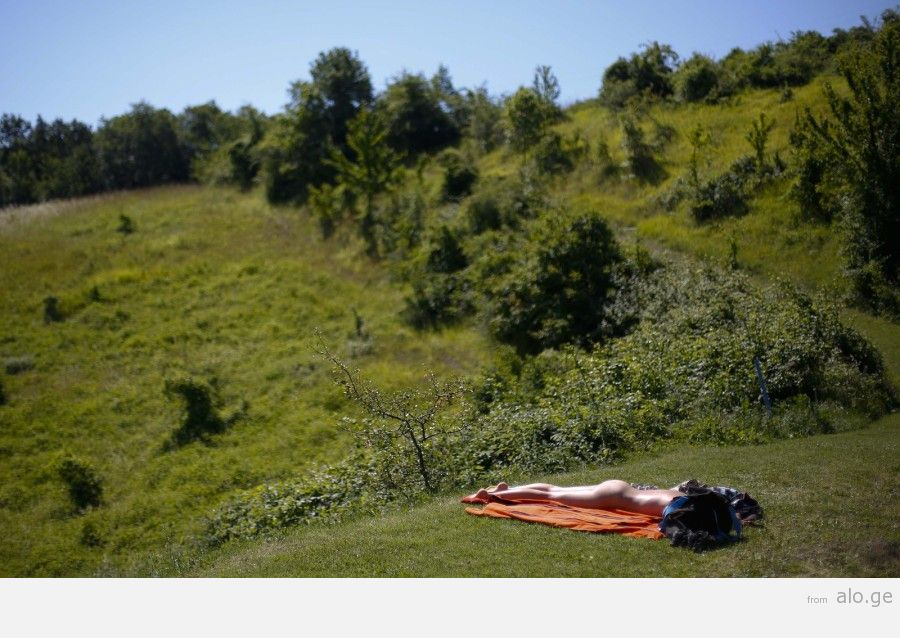"""A woman sunbathes during the """"www.inudisti.it"""" web community's annual gathering on private property at Oasis of Zello naturist resort near Bologna"""