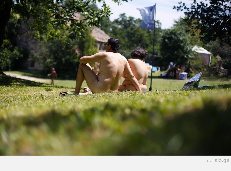 """A couple sunbathes during the """"www.inudisti.it"""" web community's annual gathering on private property at Oasis of Zello naturist resort near Bologna"""