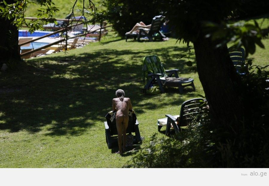 """A man rests during the """"www.inudisti.it"""" web community's annual gathering on private property at Oasis of Zello naturist resort near Bologna"""