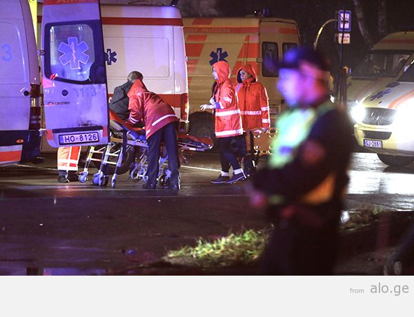 Emergency service medics take care of an injured person near a store with a collapsed roof in Riga