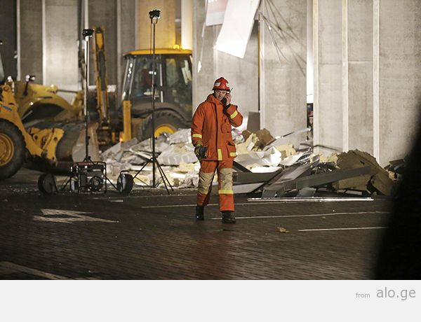 An emergency service personnel speaks on his mobile phone as he walks past the collapsed Maxima supermarket in Riga
