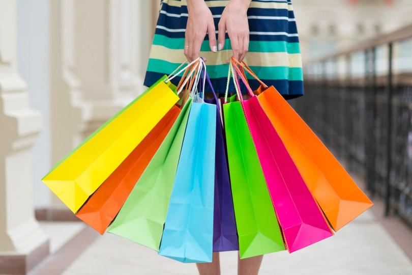 色とりどりのショッピングバッグを持った女性
