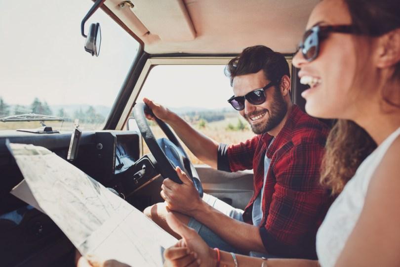 地図を見ながらドライブするカップル