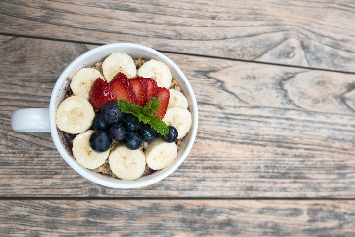 Acai bowl with strawberry, blueberry, banana, granola on wooden table.