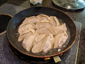 Fill the pan up with water halfway up the jiaozi and cover.