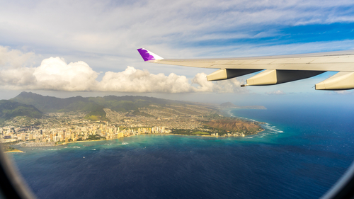 Hawaiian Airlines flight flying over Hawaii with Oahu below.