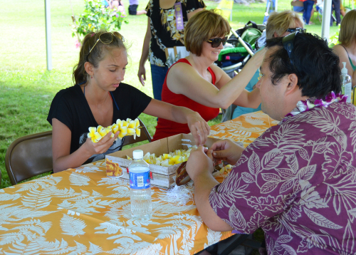 Learning how to make a lei for the first time at the Lei Day celebration. Editorial credit: Andmir / Shutterstock.com