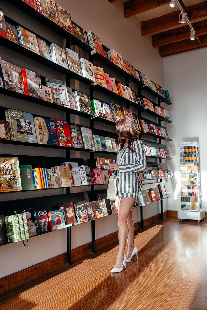Dallas blogger A Lo Profile looking at a book in a two piece striped short suit