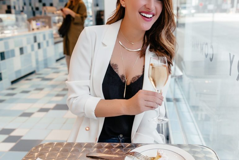 A Lo Profile wearing Kendra Scott in a restaurant with champagne and dessert