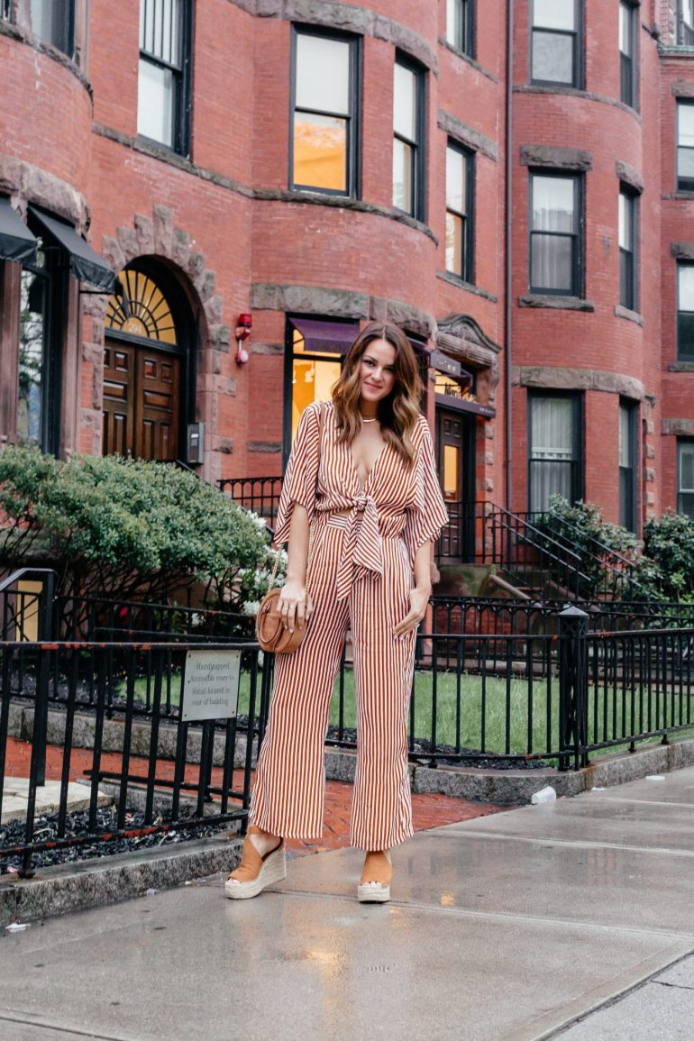 A Lo Profile wearing an orange striped Faithful the Brand Jumpsuit with tie detail paired with Marc Fisher espadrilles, and a round Rebecca Minkoff bag.