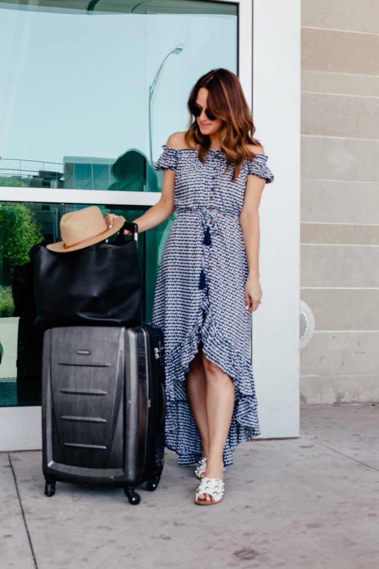 A Lo Profile wearing a Tiarre Hawaii dress with white studded March Fisher sandals, a banana republic straw hat, blue fendi sunglasses from solstice sunglasses, a black dagne dover tote, and samonsite luggage.