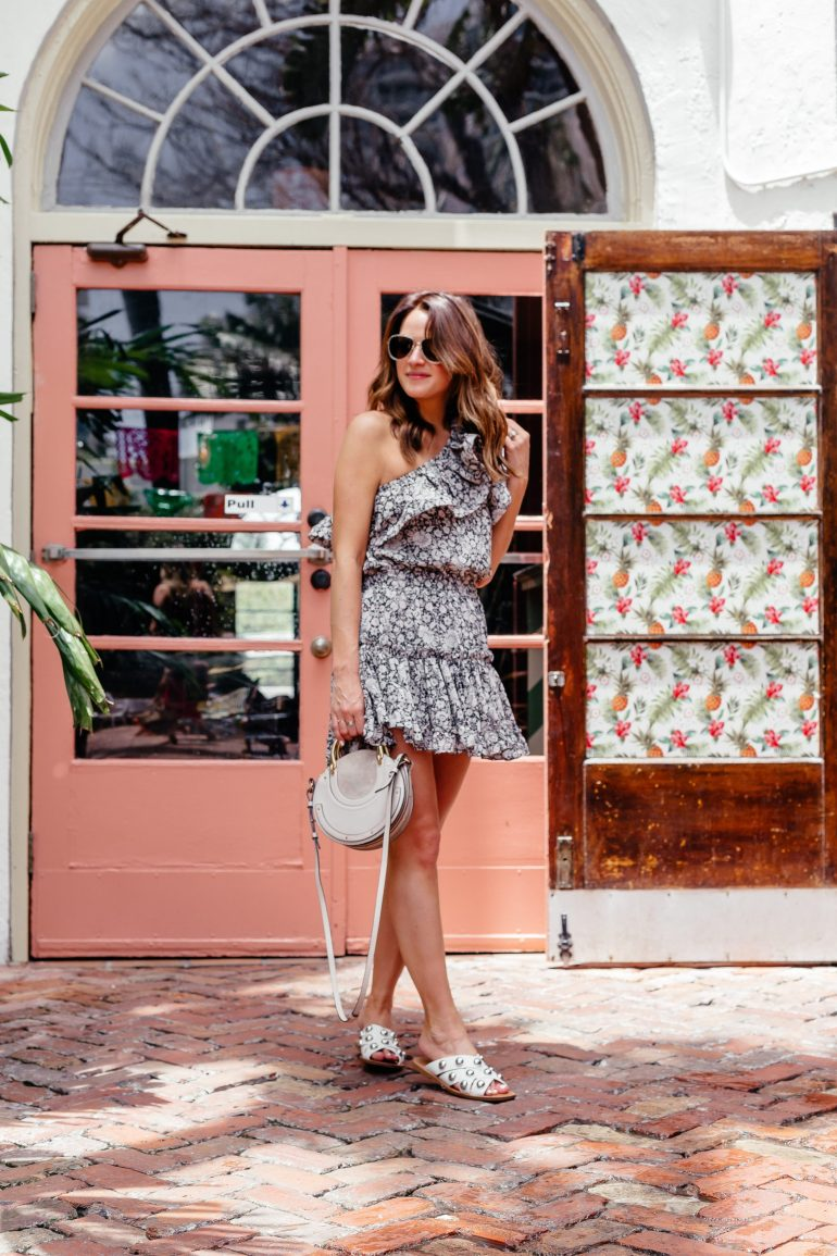 A Lo Profile wearing a one shoulder floral Misa Los Angeles dress with white studded Marc Fisher sandal, a grey Chloe round pixi bag, and glitter Gucci aviator sunnies.