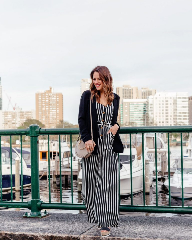 A Lo Profile wearing a black and white stripe Free People jumpsuit with black See by Chloe wedges, a black Topshop blazer, and a round gray Chloe pixie bag.