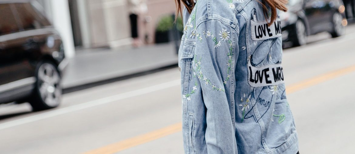 A Lo Profile wearing an embroidered denim jacket from Topshop at Nordstrom with a black dress, white booties, and white booties.
