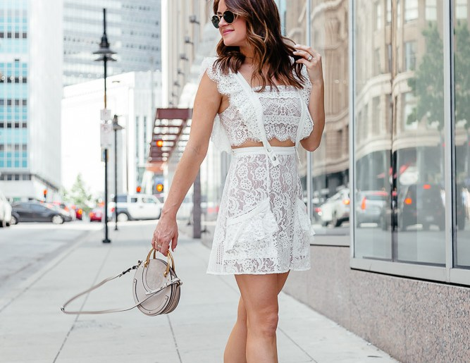 A Lo Profile wearing a white lace For Love and Lemons dress from eBay with a gray Chloe Pixie round bag, gray tassel Jeffrey Campbell block heels, and round ray ban sunglasses.