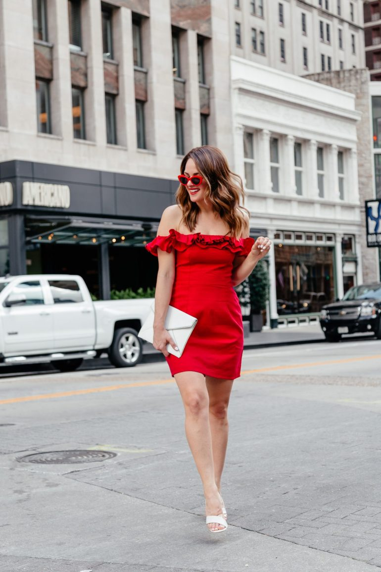 A Lo Profile wearing a little off the shoulder dress with ruffle details paired with red retro sunglasses, white and clear PLV shoes, and a white Rebecca Minkoff clutch.