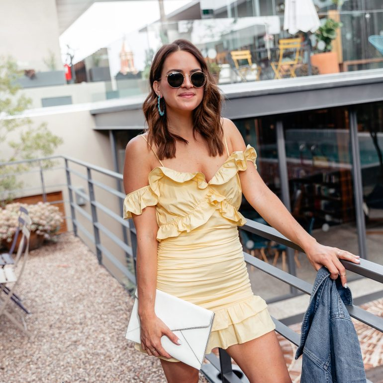 Lauren from A Lo Profile wearing a yellow ruffle dress by Lovers and Friends with a denim jacket, a white rebecca minkoff envelope clutch, turquoise bauble bare earrings, and white marc fisher sandals in San Miguel de Allende.