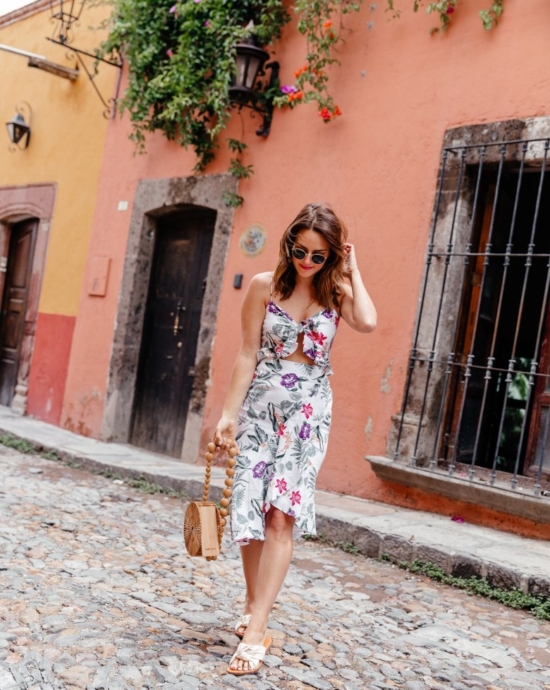 Lauren Roscopf of A Lo Profile wearing a floral print midi dress with ruffle and tie details from WAYF with a cult gaia bag, soludos sandals, and ray ban sunnies in San Miguel de Allende.