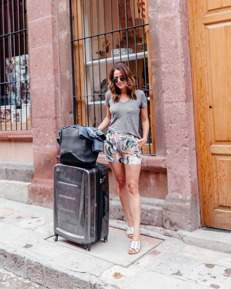 Lauren Roscopf from A Lo Profile wearing palm printed shorts with a gray tshirt for an easy travel outfit