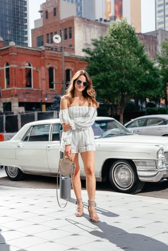 A Lo Profile wearing a blue and white stripe 1 State long sleeve romper paired with gray Jeffrey Campbell tassel block heels, a gray round Chloe pixie bag, and a blue Fendi sunglasses from Solstice Sunglasses