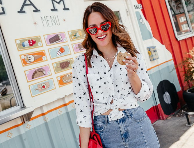 Lauren Roscopf from A Lo Profile wearing a denim skirt, a white top with blue stars, red wedges, and red heart sunnies from the Nasty Gal Americana collection for July 4th.