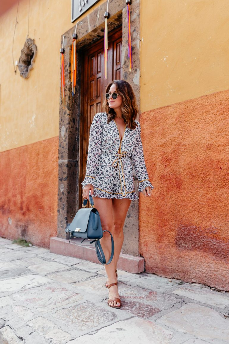 A Lo Profile wearing a floral plunging tie romper by Tularosa with tan sandals, a blue zac zac posen convertible back pack bag, and round Ray Ban sunnies in San Miguel de Allende.