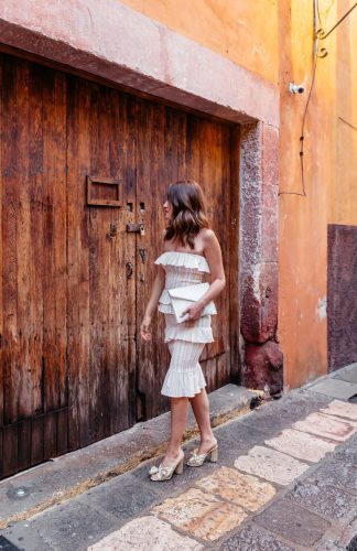 A Lo Profile wearing a ruffle tube top dress by Tula Rosa with gold Loeffler Randall shoes, a white rebecca minkoff envelope clutch, and white hoop earrings from Bauble Bar in San Miguel de Allende.